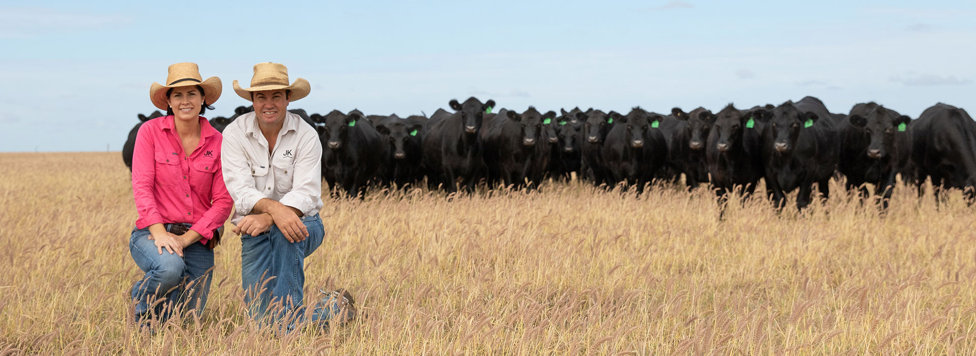 Justin and Kate Boshammer kneeling in front of Angus cattle